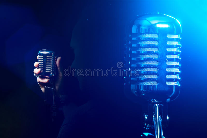 Микрофон металла на голубой предпосылке Певица поет песню o стоковые фотографии rf