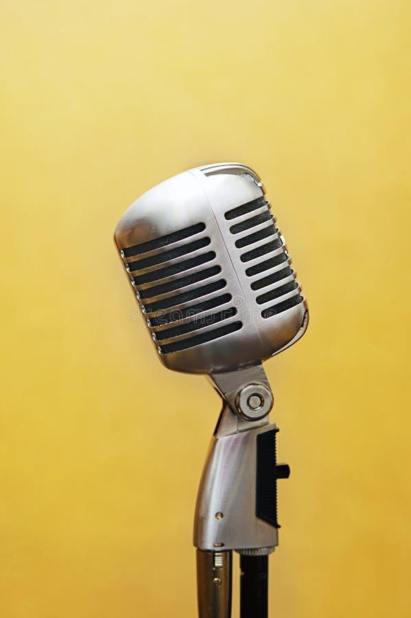 микрофон над желтым цветом студии вокальным стоковое фото