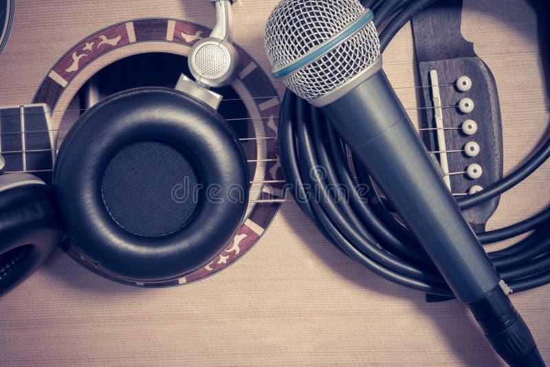 Микрофон, наушники на предпосылке гитары стоковое изображение