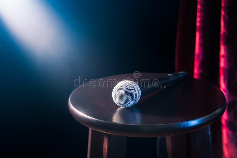 Микрофон на деревянной табуретке на этапе комедии стойки вверх с рефлекторами излучает, сверхконтрастное изображение стоковые фото