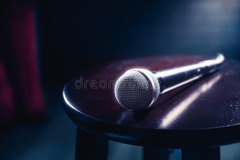 Микрофон на деревянной табуретке на этапе стоковое фото