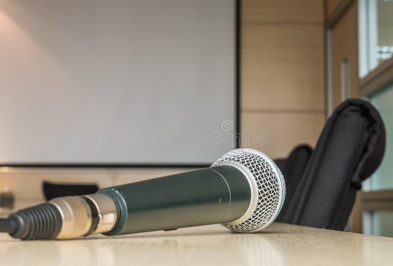 Микрофон на деревянном столе в конференц-зале под светом окна стоковые изображения rf