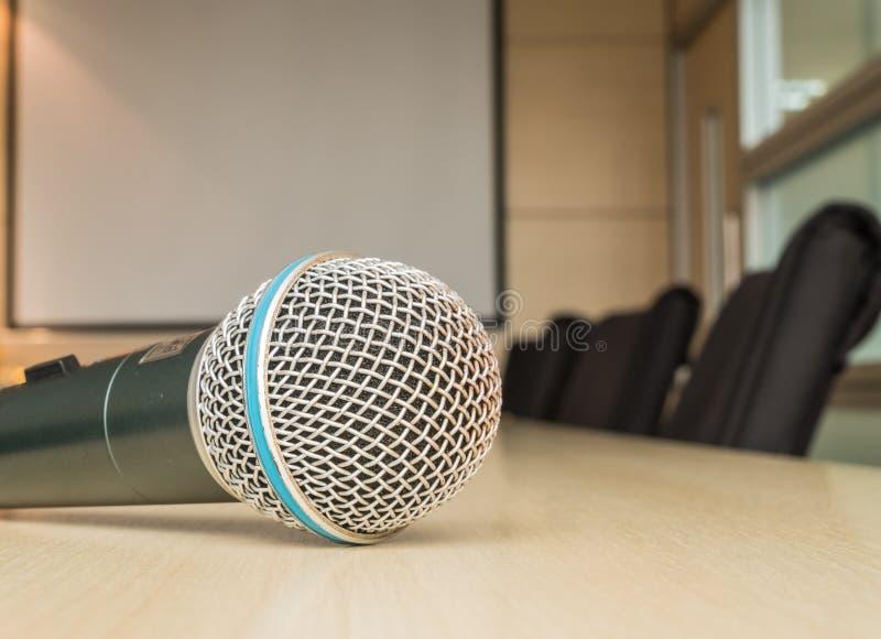 Микрофон на деревянном столе в конференц-зале под светом окна стоковая фотография