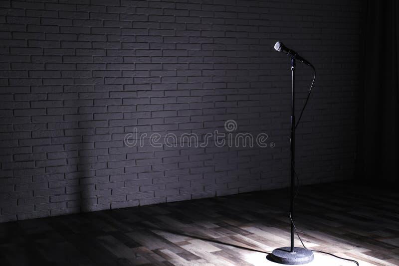 Микрофон на темном этапе около кирпичной стены стоковая фотография rf