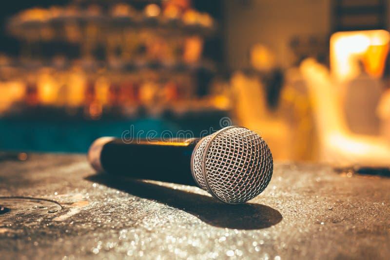 Микрофон на том основании и запачканное фото предпосылки конференц-зала или конференц-зала или комнаты свадьбы стоковое изображение