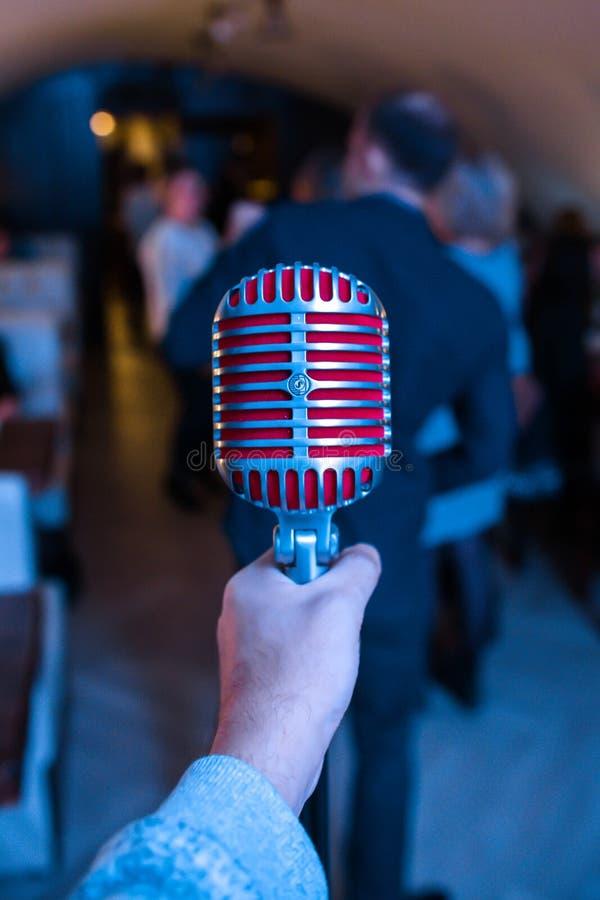 Микрофон на этапе в ночном клубе Певица держит и поет в микрофон Яркий свет блеска клуба на MIC стоковое изображение rf