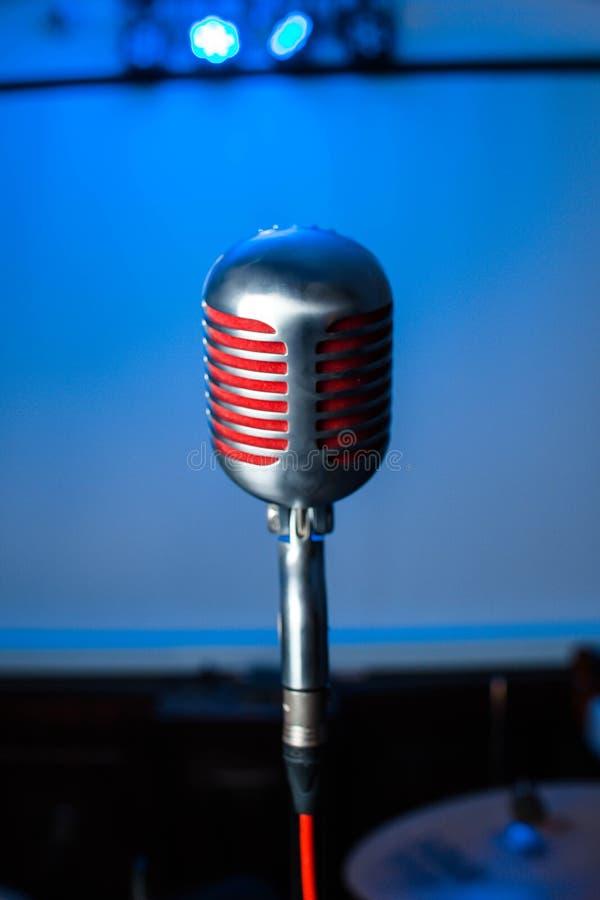 Микрофон на этапе в ночном клубе Певица держит и поет в микрофон Яркий свет блеска клуба на MIC стоковые изображения rf