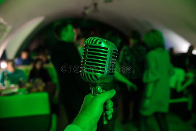 Микрофон на этапе в ночном клубе Певица держит и поет в микрофон Яркий свет блеска клуба на MIC стоковая фотография