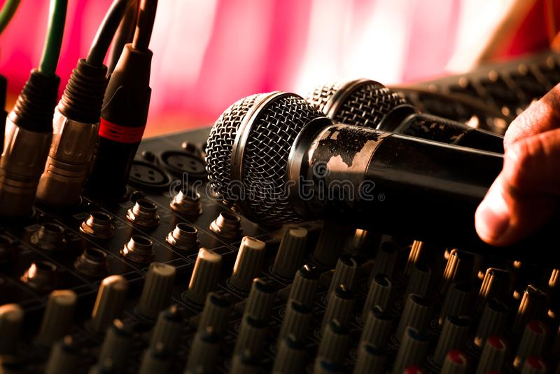 Микрофон помещенный на тональнозвуковой музыке управлением смесителя в партии стоковые фото
