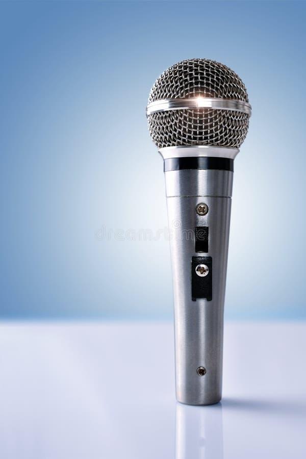 Микрофон при отражения стоя на белой таблице и голубом bac стоковые фото