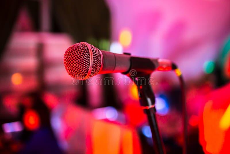 Микрофон стоит на этапе в ночном клубе Яркие блески света клуба на MIC Представления в ночном клубе стоковые фотографии rf