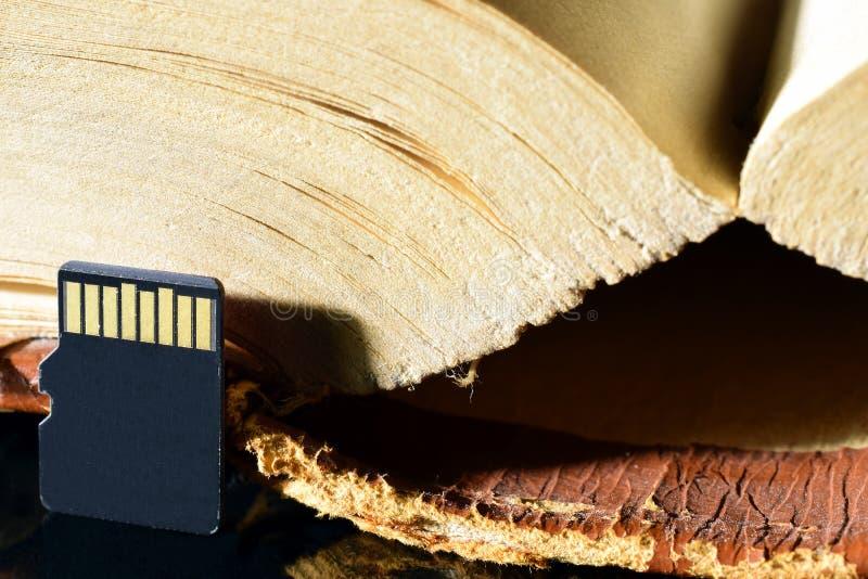 Микро- карта памяти sd и старая толстая книга стоковая фотография rf