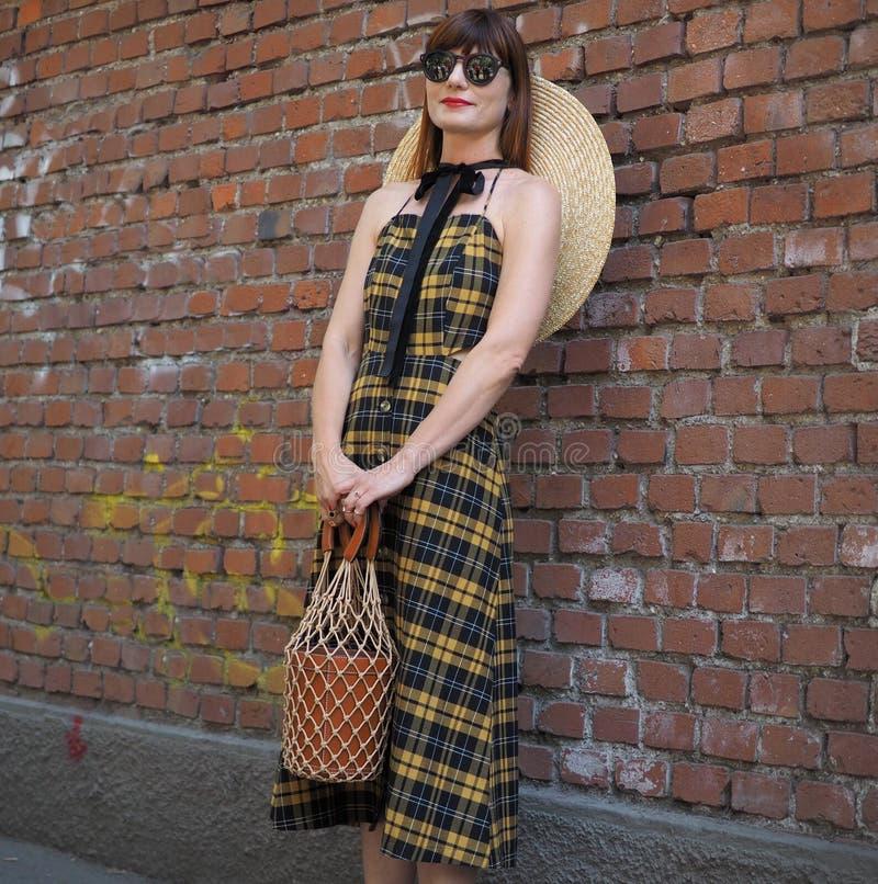 МИЛАН, ИТАЛИЯ - 18-ОЕ ИЮНЯ 2018: Модная женщина представляя для фотографов в улице перед модным парадом FENDI, стоковые изображения