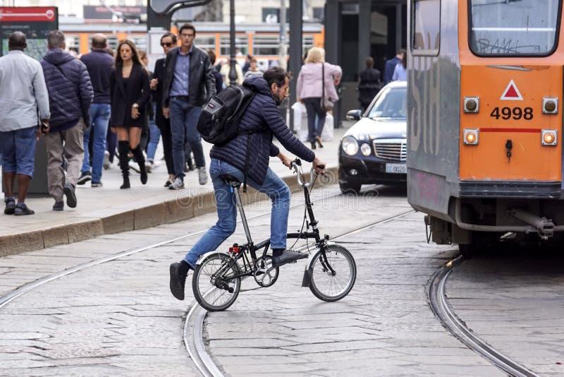 Милан, Италия - 4-ое мая 2018: человек посещает город используя велосипед складчатости этот середины перехода удобные быстрые и стоковые фото