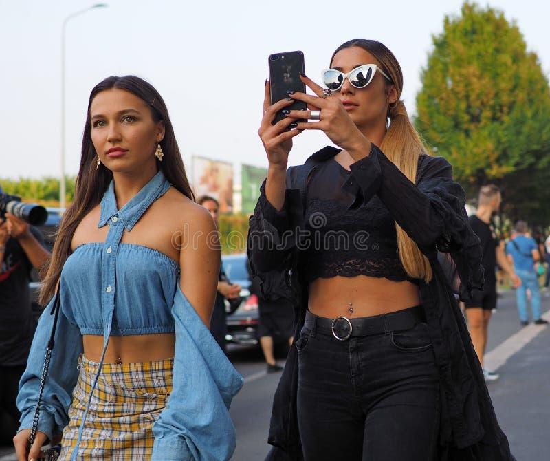МИЛАН, Италия 20-ОЕ СЕНТЯБРЯ: Фотографы обмундирования стиля улицы женщин стоковое фото
