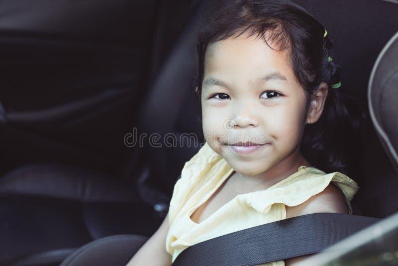 Милая азиатская девушка маленького ребенка сидя в автокресле стоковые фотографии rf