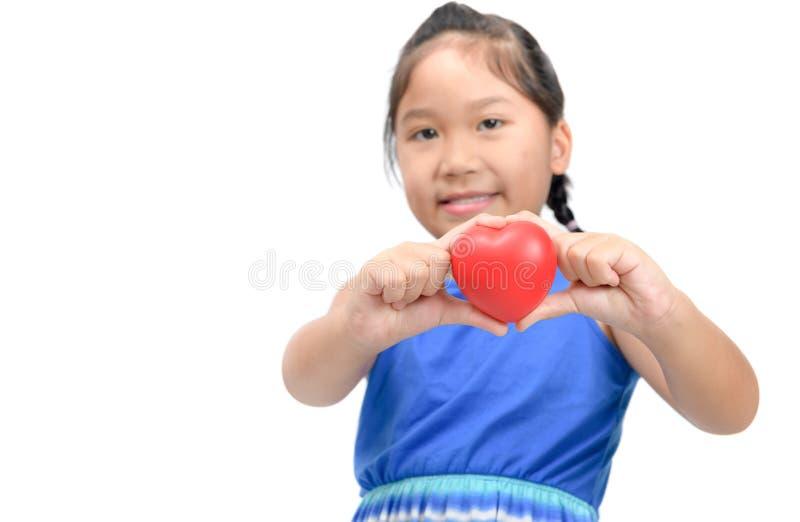 Милая азиатская девушка показывает меньшее красное сердце в изолированной руке стоковое изображение rf