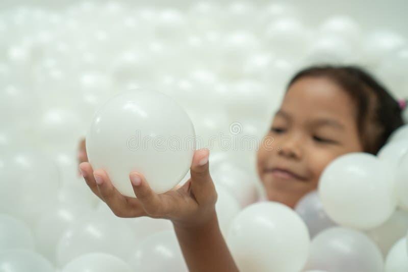 Милая азиатская девушка ребенка держа шарик и имея потеху для игры с белыми пластиковыми шариками стоковое фото