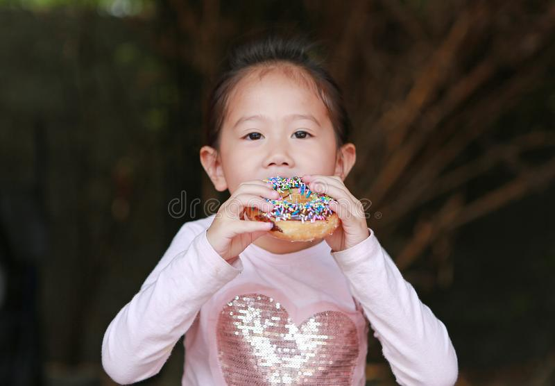 Милая азиатская девушка ребенка наслаждается съесть донут радуги стоковые фото