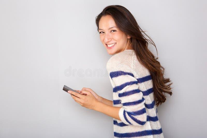 Милая азиатская женщина усмехаясь с мобильным телефоном против серой предпосылки стоковое фото rf