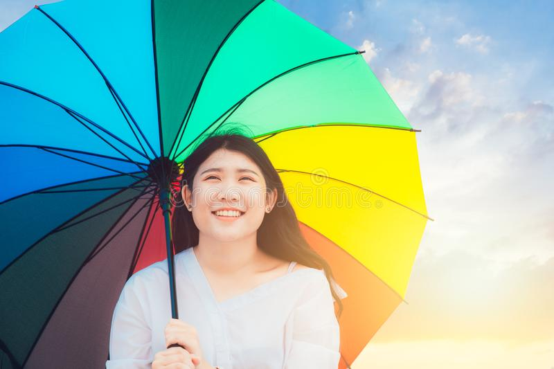 Милая азиатская предназначенная для подростков счастливая улыбка внешняя с зонтиком радуги красочным стоковые изображения rf