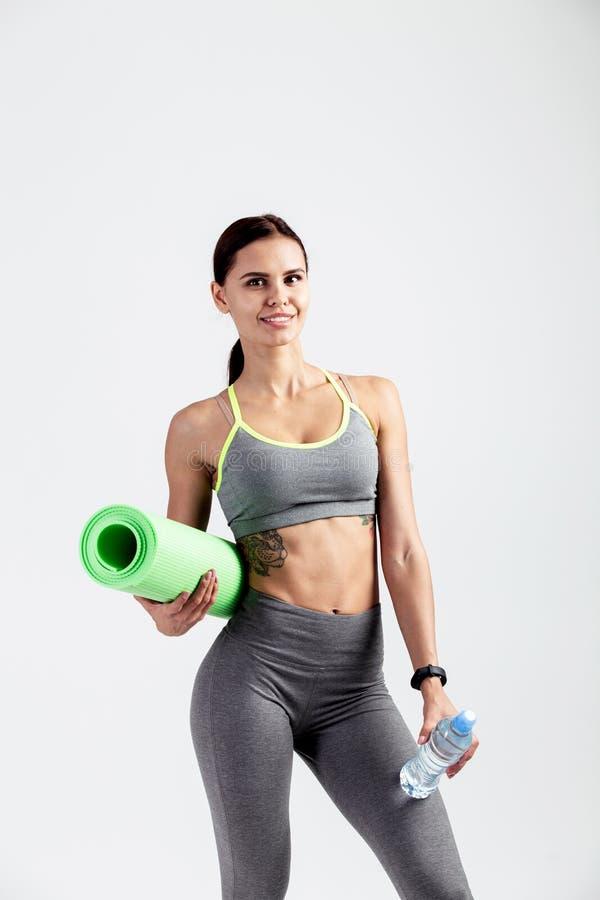 Милая атлетическая девушка одетая в сером sportswear стоит с циновкой фитнеса и бутылкой воды в ее руках на стоковые фотографии rf
