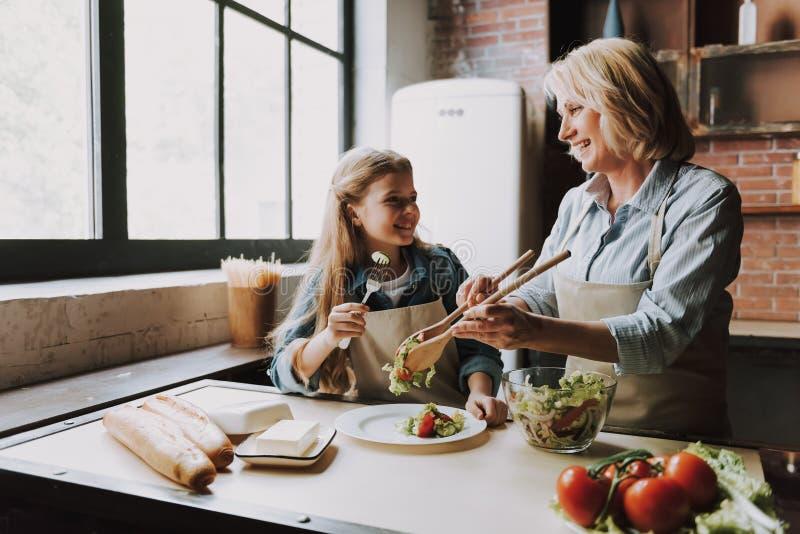 Милая бабушка и внучка варя салат стоковые изображения rf