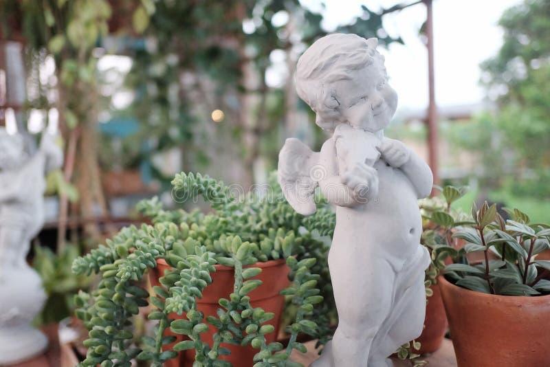 Милая белая скульптура купидона играя скрипку и вытаращить в зеленом саде с запачканными предпосылкой природы и светом bokeh стоковое фото rf