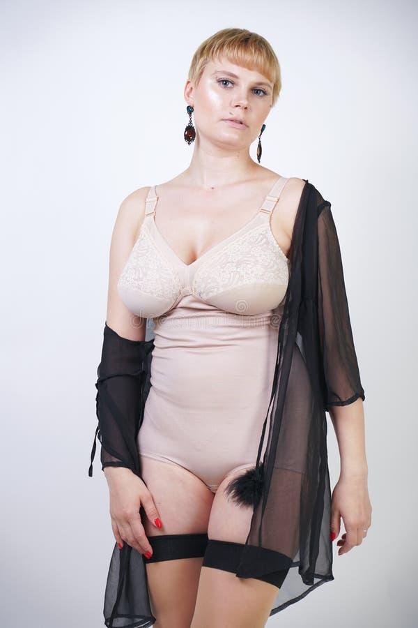 Милая белокурая женщина коротких волос ретро с curvy телом представляя в бежевом винтажном bodysuit и сексуальных классических чу стоковое фото