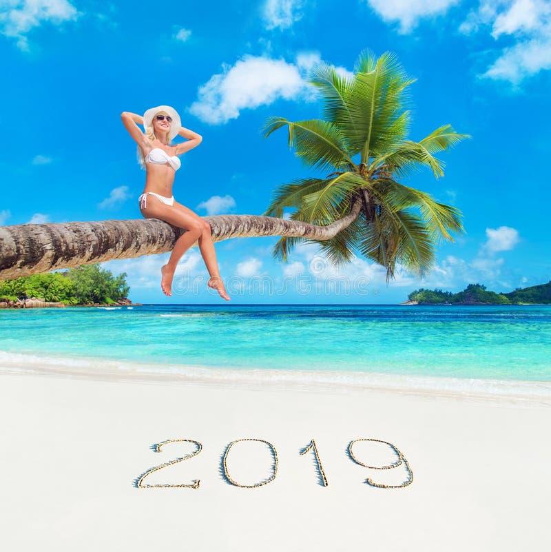 Милая белокурая женщина на пальме против тропического пляжа океана, концепции 2019 сезона стоковые изображения