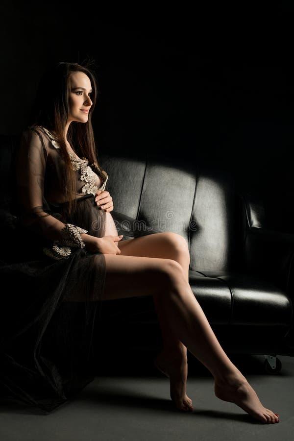 Милая беременная девушка в халате в темноте стоковое изображение