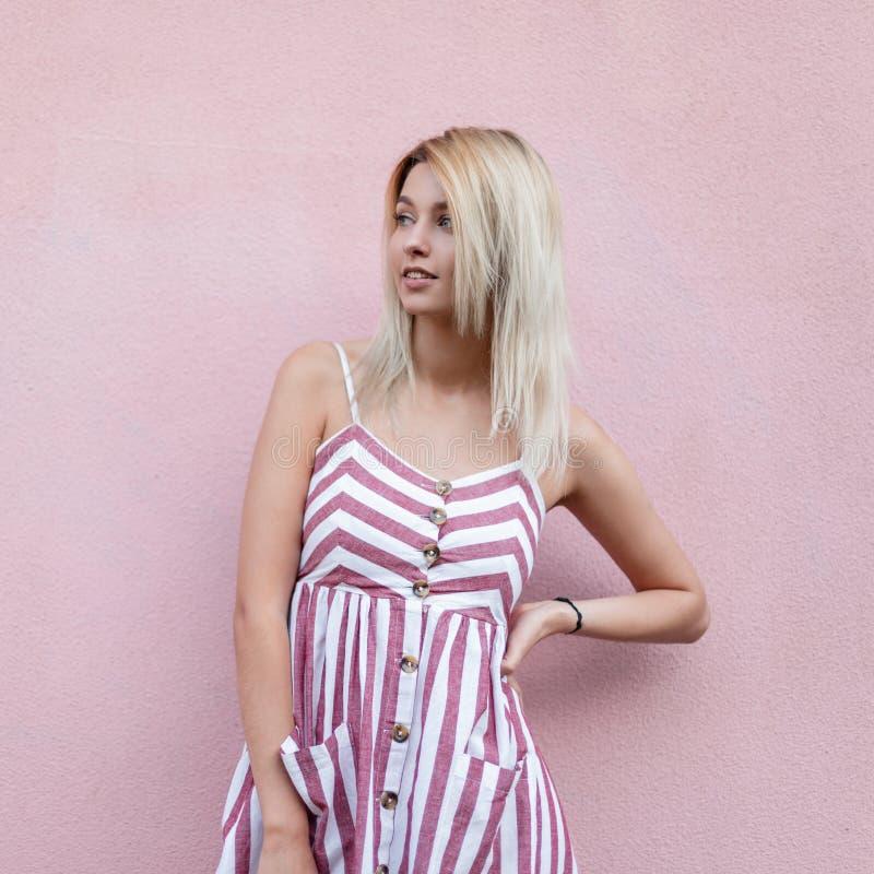 Милая блестящая молодая женщина с милой улыбкой со светлыми волосами в модном striped розовом платье представляя положение стоковые фотографии rf