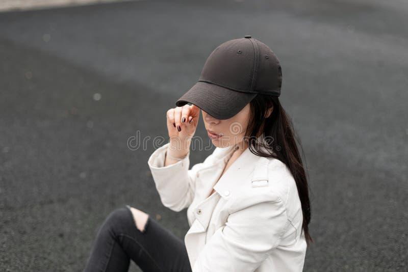 Милая городская молодая женщина в модной черной бейсбольной кепке в стильной белой кожаной куртке ослабляет и смотрит вниз outdoo стоковая фотография rf