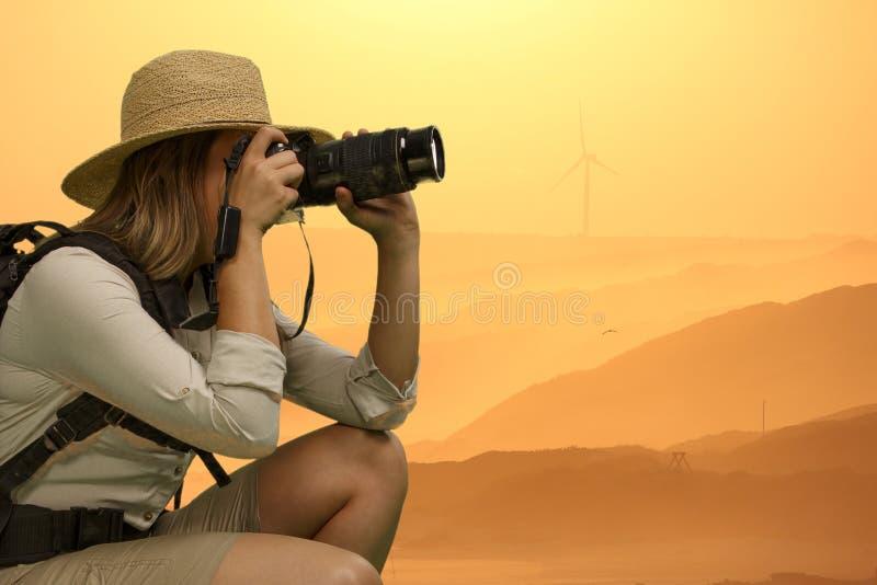 Милая дама в платье сафари принимая фотоснимки на заход солнца стоковые изображения rf