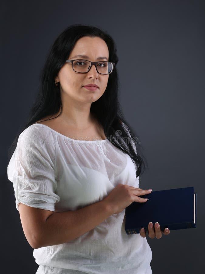 Милая дама держит голубую книгу стоковые фото