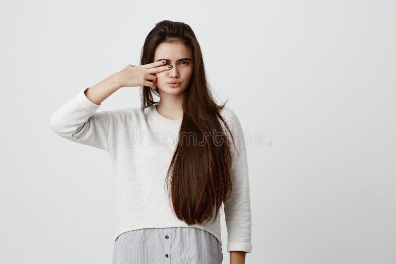 Милая девушка брюнет с длинными волосами, делающ стороны, pouting губы, закрывая одно из ее глаза с знаком v, имеющ довольное стоковое изображение rf