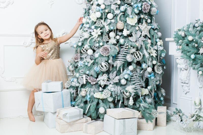Милая девушка внутри украшает рождественскую елку стоковые фотографии rf