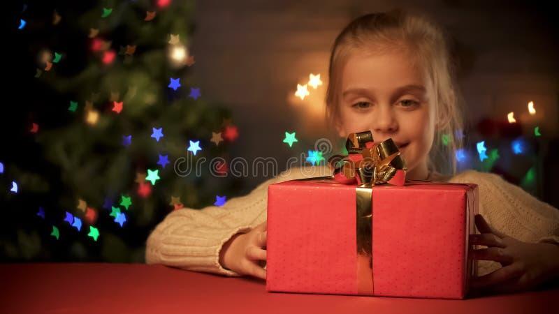 Милая девушка восхищая красную подарочную коробку с большим золотым смычком, мечтами ребенка, волшебством xmas стоковые фото
