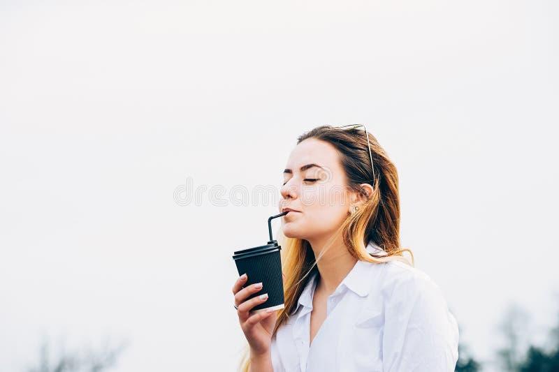 Милая девушка выпивая коктеиль, усмехаясь, глаза закрыла, sp экземпляра стоковое изображение rf