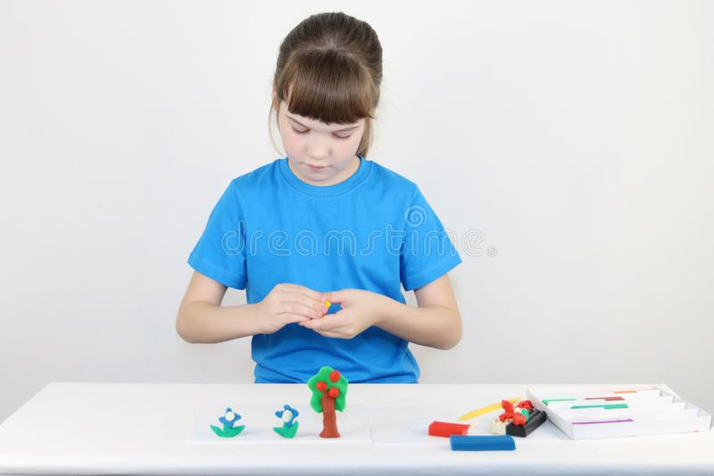 Милая девушка в голубых прессформах от пластилина на белой таблице стоковое фото
