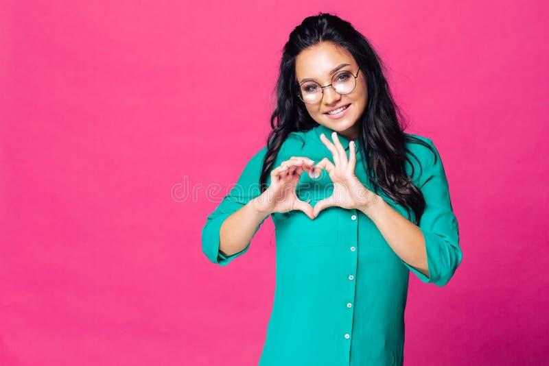 Милая девушка в зеленой блузке на розовой предпосылке показывает сердце из руки стоковое фото