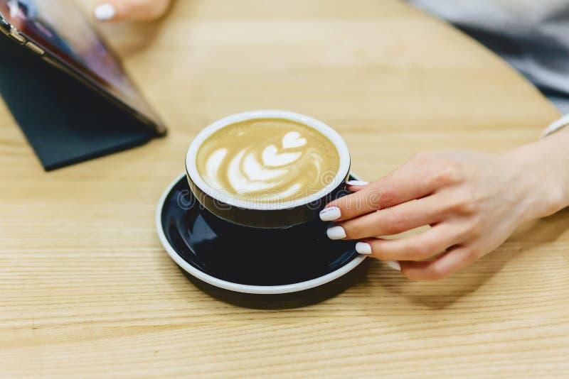 Милая девушка в кафе выпивает кофе и работает стоковое фото rf
