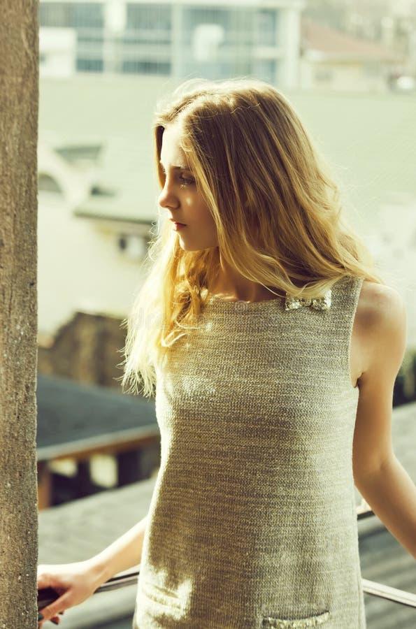 Милая девушка в модном сером платье на балконе стоковые фотографии rf