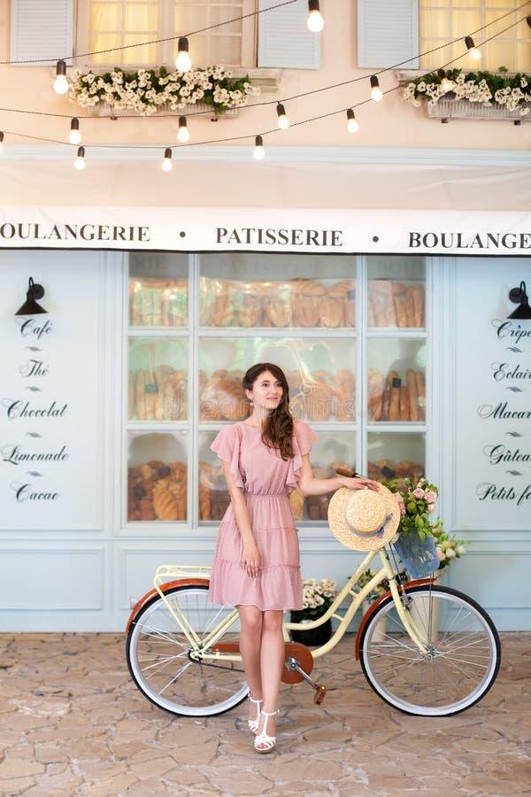 Милая девушка в платье и с соломенной шляпой стоит с желтым ретро велосипедом в европейском городе На предпосылке c стоковые фотографии rf