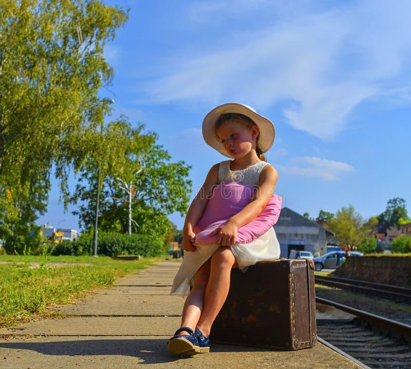 Милая девушка держа игрушку плюша на железнодорожном вокзале, ждать поезд с винтажным чемоданом Жулик путешествовать, праздника и стоковые фотографии rf
