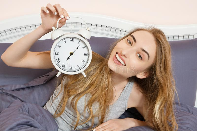 Милая девушка держит часы и лож в спальне кровати Эмоциональная красивая женщина лежа в кровати на ее выходной стоковые изображения