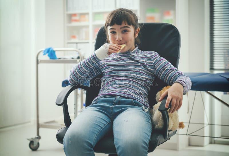 Милая девушка есть закуску в офисе доктора стоковое фото