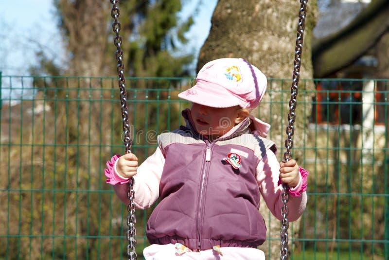 Милая девушка играя на качании стоковые фото