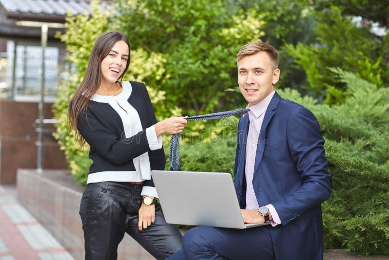 Милая девушка и красивый парень работают в парке на компьютере на естественной предпосылке стоковое фото rf