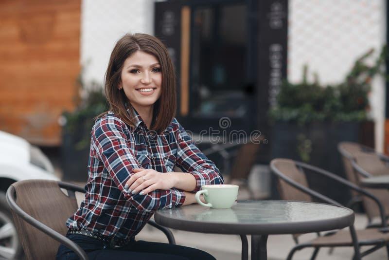Милая девушка, красивое брюнет с элегантным стилем причёсок в рубашке шотландки выпивает чашку кофе outdoors в кафе лета стоковые фото